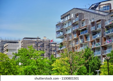 Paris, France - June 28, 2015: Eco-Quartier Clichy-Batignolles. New Modern Architecture. Park Martin Luther King. Green tree crowns and building facades with balconies