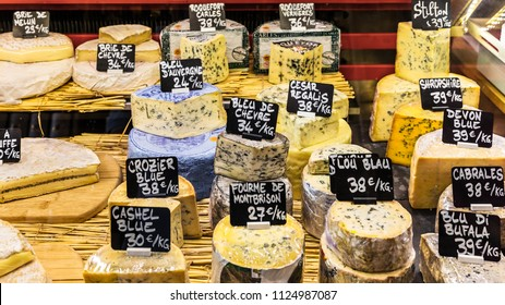 Paris, France - June 29, 2017:  A large selection of different french and italian cheeses on the counter of a small store at the Aligre Market (Marche d'Aligre) in the Bastille district.