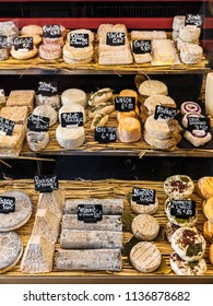 Paris, France - June 29, 2017:  A large selection of different french and italian cheeses on the counter of a small store at the market in the Bastille district.