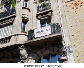 """PARIS, FRANCE - JUNE 29, 2018: A banner is displayed on a balcony asking for """"silence, droit au sommeil"""" -silence right to sleep in English- on June 29, 2018 in Paris, France."""