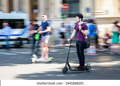 Paris, France - June 29, 2019: A relaxed young man rides with one hand an electric scooter at high speed, without helmet nor protection, overtaking another man on an electric scooter on the roadway.