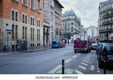 Paris,  France - June 3, 2017: Small refrigerated truck of Orca Maree company stands on the Rue Saint-Jacques. In both sides there are buildings with roof apartments. Parked cars seen along the street