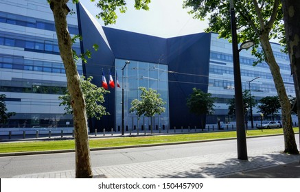 Paris, France - June 30, 2019 - Main entrance of Hexagone Balard, new seat of the French Ministry of Defence, flying three French flags