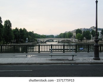 Paris, France - June 5 2011:  Cityscape of arched bridge over the Seine river at dawn with no people against a cool grey sky with green trees on Left Bank and  classic buildings on the Right Bank