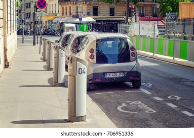 Paris, France - June 5, 2017: Back view of rental car station Autolib is located at 66 Rue Henri Barbusse. Three electric autos are charging here. One recharging unit without car us seen in foreground