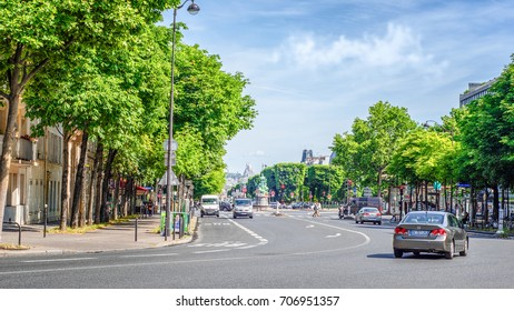 Paris, France - June 5, 2017: Front view of Avenue de l'Observatoire flanked by tall green trees from both sides.Cars moving on wide asphalt road. Monument of Francis Garnier is seen in the background