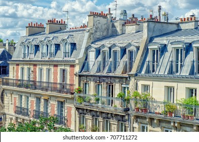 Paris,  France - June 5, 2017: Side view of attic apartments are located on four story buildings at Rue de l'Abbe de l'Epee. Green plants grow in pots in balconies on lower floors. Sunny summer day
