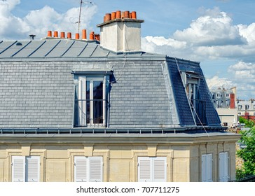 Paris,  France - June 5, 2017: View of classical Parisian attic apartment with gray tiled facade covered by roofing iron sheets and big chimney. Close up shot was taken in Latin Quarter in sunny day