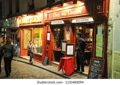 Paris, France - june 6, 2008: People walking through the streets of the Montmartre district, next to the doors of bars and shops in the area, at dusk