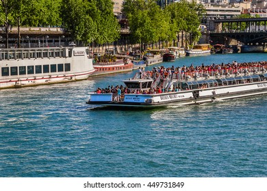 PARIS, FRANCE - JUNE 6, 2015: View of the Seine River with cruise tour boats near Eiffel tower. In Paris there are several boat tourist trips across the Seine to show tourists the sights of interest.