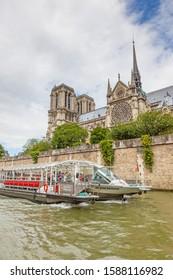 PARIS, FRANCE - JUNE 8, 2012:  The cruise boat Catherine Deneuve on the River Seine motors past Notre Dame Cathedral in Paris.