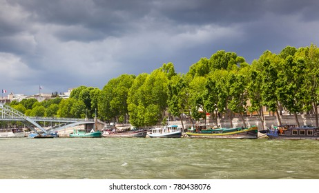 PARIS, FRANCE - JUNE 8, 2012: Colorful boats moored alongside the River Seine in Paris, with storm clouds in the background.