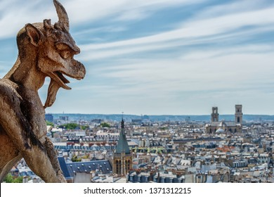 Paris France. - June 8, 2017: Detail of one of the gargoyles of Notre Dame Cathedral looking at Paris on a warm June afternoon.