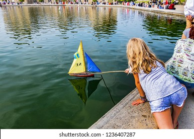 PARIS, FRANCE - JUNE 9, 2018: Traditional small wooden sailing boat in Luxembourg Garden (Jardin du Luxembourg) pond. Jardin du Luxembourg - second largest Public Park in Paris.