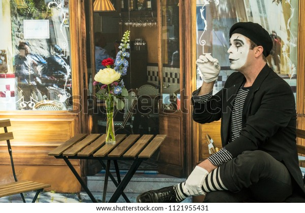 PARIS, FRANCE - June 9, 2018: Mime in front of Paris cafe acting like drinking tea or coffee.