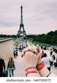 Paris, France - June 9, 2019: Two holding hands with Speak Yourself red bracelets by K-pop popular famous band BTS, Bangtan Boys in front of Eiffel Tower among green trees during summer day