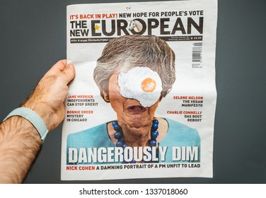 Paris, France - Mar 12, 2019: Man holding against gray background The New European magazine with portrait of Theresa May and title Dangerously Dim - Brexit news for the 48 percent