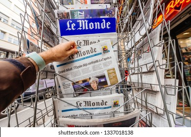 Paris, France - Mar 12, 2019: Man buying from kisok stand French newspaper Le Monde featuring on the cover Theresa May and last deals about Brexit