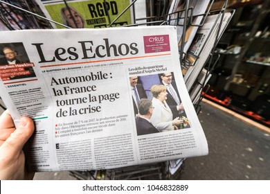 PARIS, FRANCE - MAR 15, 2017: Man reading buying French Les Echos newspaper at press kiosk featuring Angela Dorothea Merkel re election as Chancellor of Germany