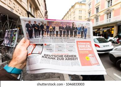 PARIS, FRANCE - MAR 15, 2017: Man reading buying German newspaper at press kiosk featuring Angela Dorothea Merkel government team