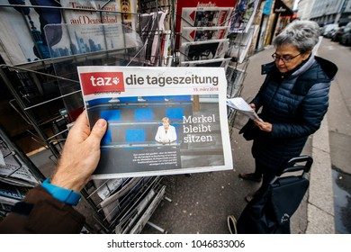 PARIS, FRANCE - MAR 15, 2017: Man reading buying German die tageszeitung newspaper at press kiosk featuring Angela Dorothea Merkel re election as Chancellor of Germany