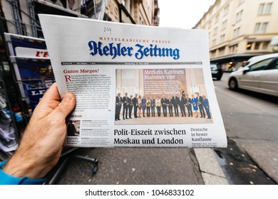 PARIS, FRANCE - MAR 15, 2017: Man reading buying German Kehler Zeitung newspaper at press kiosk featuring Angela Dorothea Merkel re election as Chancellor of Germany team