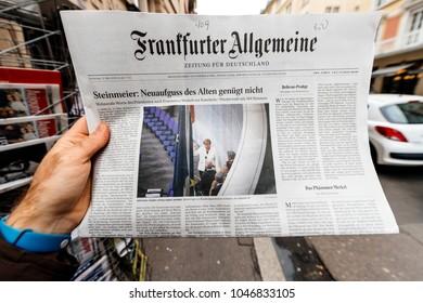 PARIS, FRANCE - MAR 15, 2017: Man reading buying German Frankfurter Allgemeine Zeitung newspaper at press kiosk featuring Angela Dorothea Merkel re election as Chancellor of Germany