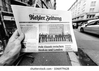 PARIS, FRANCE - MAR 15, 2017: Man reading buying German Kehler Zeitung newspaper at press kiosk featuring Angela Dorothea Merkel re election as Chancellor of Germany team