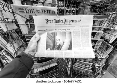 PARIS, FRANCE - MAR 15, 2017: Man reading buying German Frankfurter Allgemeine Zeitung newspaper at press kiosk featuring Angela Dorothea Merkel re election as Chancellor of Germany