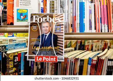 PARIS, FRANCE - MAR 15, 2018: Top of billionaires in France as of Forbes Magazine with portrait of LVMH owner Bernard Arnault at press kiosk