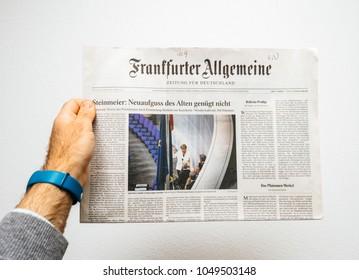 PARIS, FRANCE - MAR 15, 2018: Man reading German Frankfurter Allgemeine Zeitung newspaper at press kiosk featuring Angela Dorothea Merkel re election as Chancellor of Germany