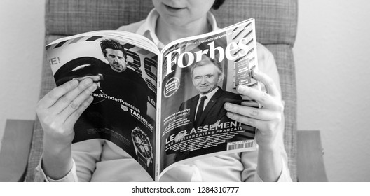 Paris, France - Mar 16, 2018: Black and white image of young business woman reading The World's Billionaires List in Forbes magazine with LVMH CEO Bernard Arnault on cover
