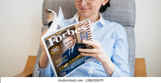 Paris, France - Mar 16, 2018: Young business woman reading The World's Billionaires List in Forbes magazine with LVMH CEO Bernard Arnault on cover