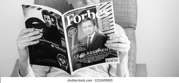 Paris, France - Mar 16, 2018: Woman reading in office Forbes Magazine featuring the top of the richest fortunes in France