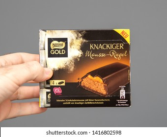 PAris, France  - Mar 16, 2019: Man hand holding against gray background sweet Nestle Gold Knackiger Mousse-Riegel sweets bars