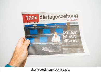 PARIS, FRANCE - MAR 19, 2017: Man reading German die tageszeitung newspaper at press kiosk featuring Angela Dorothea Merkel re election as Chancellor of Germany