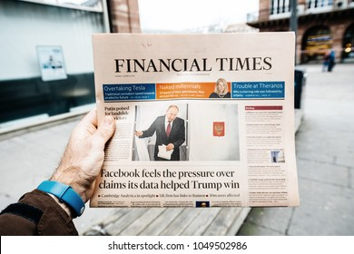 PARIS, FRANCE - MAR 19, 2018: Man reading buying British Financial Times newspaper at press kiosk featuring Russian presidential election from 2018 with the winner Vladimir Putin