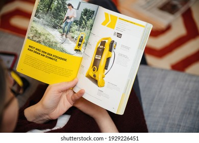 Paris, France - Mar 2, 2021: Curious woman reading latest advertising catalogue of Karcher German family-owned company that operates worldwide and is known for its high-pressure cleaners,
