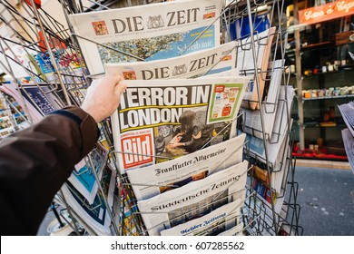 PARIS, FRANCE - MAR 23, 2017: POV Man purchases newspaper German Bild from press kiosk newsstand featuring Terror in London headlines following  terrorist incident in London  Westminster Bridge