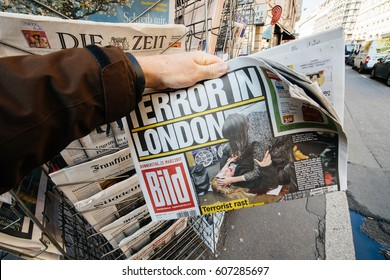 PARIS, FRANCE - MAR 23, 2017: Man purchases a   newspaper German Bild from press kiosk newsstand featuring Terror in London headlines following terrorist incident in London at the Westminster Bridge