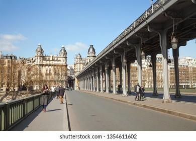 Paris, France - MAR 26, 2019: People are walking on Bir-Hakeim bridge in warm spring day