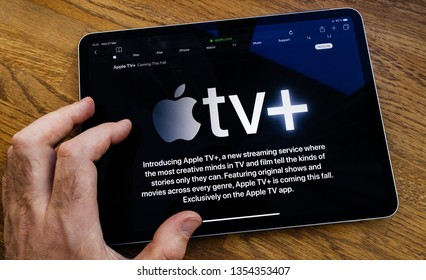 Paris, France - Mar 27, 2019: POV man reading on iPad Pro about Apple TV Plus streaming service