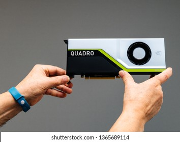 Paris, France - Mar 28 2019: Senior man showing latest Nvidia Quadro RTX 5000 workstation GPU with texture mapping units, render output units, streaming multiprocessors, tensor cores gray background