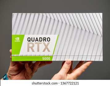Paris; France - Mar 28 2019: Senior man showing cardboard boxes before unboxing of Nvidia Quadro RTX 5000 workstation GPU featuring new streaming multiprocessors; tensor cores - gray background
