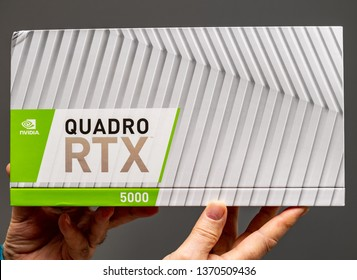 Paris; France - Mar 28 2019: Senior man showing cardboard boxes before unboxing of Nvidia Quadro RTX 5000 workstation GPU featuring new tensor cores - gray background