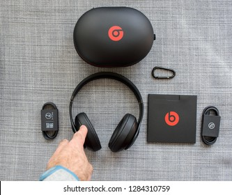 PARIS, FRANCE - MAR 31, 2018: Man hand taking new Beats 3 Studio professional wireless headphones made by Beats by Dr Dre Apple with all the accesories