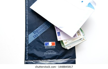 Paris, France - Mar 5 2019: Blue envelope of declaration des revenus income statement instruction with pre-filled income statement to French authorities and income tax previous year and stack of Euros