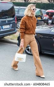 PARIS, FRANCE - MARCH 03, 2017: Anne-Laure Mais wearing a brown knut, brown pants, Dior bag outside Dior during the Paris Fashion Week Womenswear Fall/Winter 2017/2018