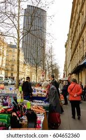 PARIS, FRANCE - MARCH 11, 2017: Senior woman choosing book at Parisian flea market and Tour Montparnasse at background. Urban scene.