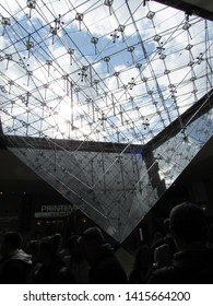 Paris, France - March 13 2019: View of the inverted pyramid within the Louvre on a cloudy day